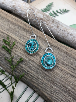 I have always loved turquoise - full of a spectrum of blues, browns and greens - since foraging through my mother's jewelry box as a child and finding massive turquoise rings to wear on each finger. In these everyday wearable earrings, I used dainty turquoise ovals and adorned them with a halo of faceted American-mined turquoise gems.  Set in sterling silver and finished with hand forged French wires.   Product Details:  • 2 Hubei-mined oval turquoise cabochons • 36 faceted American-mi