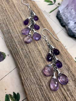 """Compassion is an action word with no boundaries"" - Prince  Bask in the gentle glow of purple amethyst drops. Pear-shaped and faceted gems are wire wrapped along a silver chain and finished on standard French wires. A cascade of color perfect for any elegant ensemble. The perfect gift for a February birthday.  Product Details:  • Sterling silver ear wires • Fourteen purple amethyst briolette gems • Sterling and fine silver • Approximately 2"" long and just over 2.25"" long from the top o"