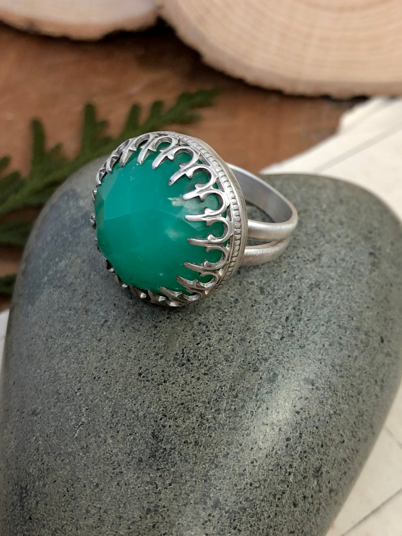 """Be kind, for everyone you meet is fighting a harder battle."" - Plato  An incredible rosecut round of chrysoprase is expertly prong set to showcase its beauty. Handcrafted in fine and sterling silver with maximal sparkle factor. Finished on a split shank for stability and comfort in a size 7.  Product Details:  • Rosecut chrysoprase round gem • Sterling and fine silver • Size 7 split shank"