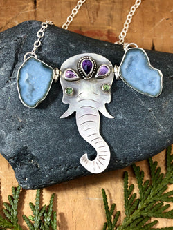 It turns out that the largest living land mammals are also among the most compassionate creatures on earth. Elephants show all kinds of emotions we associate as being human...anger, grief, joy, love...and compassion. A gentle reminder of both the complexity and simplicity of these miracles of Mother Nature.   This is 'Ellie' she's hand-forged from solid sterling and fine silver with amethyst adornments on her head and green tourmaline eyes. She also has asymmetrical ears (because, let'