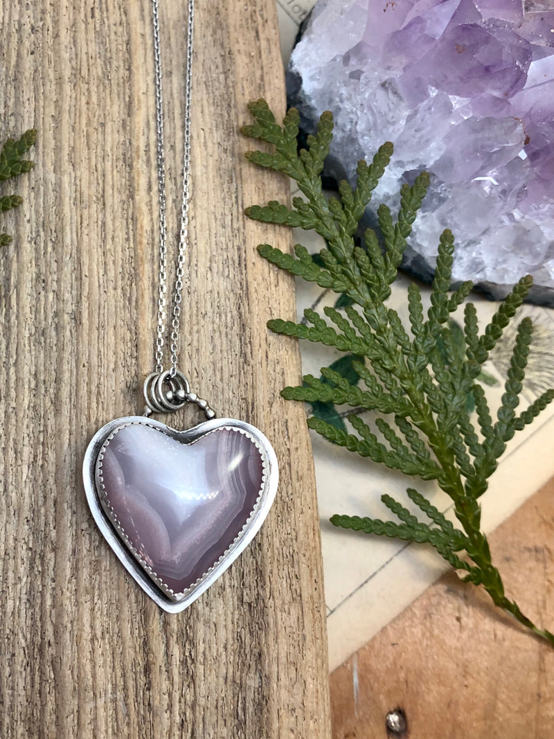 """In the end, only kindness matters."" - Jewel  An inspiring cut of Laguna agate with hues of lovely lavender reminds us to open our hearts and let the good in. Let the kindness and compassion in so that we can spread it gently into every facet of our lives. Lovingly handcrafted in fine and sterling silver with a bail of silver balls and a 20 inch chain to hang right over your heart. Finished with a sterling lobster clasp.  Product Details:  • Laguna agate heart cabochon • Sterling and f"