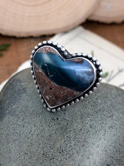 """Be kind, for everyone you meet is fighting a harder battle."" - Plato  Glimpse where the sand meets the sea and where the sea meets the clouds in this incredible and rare needles blue agate heart gem. The heart is lovingly encased in fine silver with an accent of solid sterling silver beads around its border. Finished on a sterling silver split shank in size 8 and comfortable enough for everyday wear. Remember who you are, what you mean to others and where your heart feels at home...by"