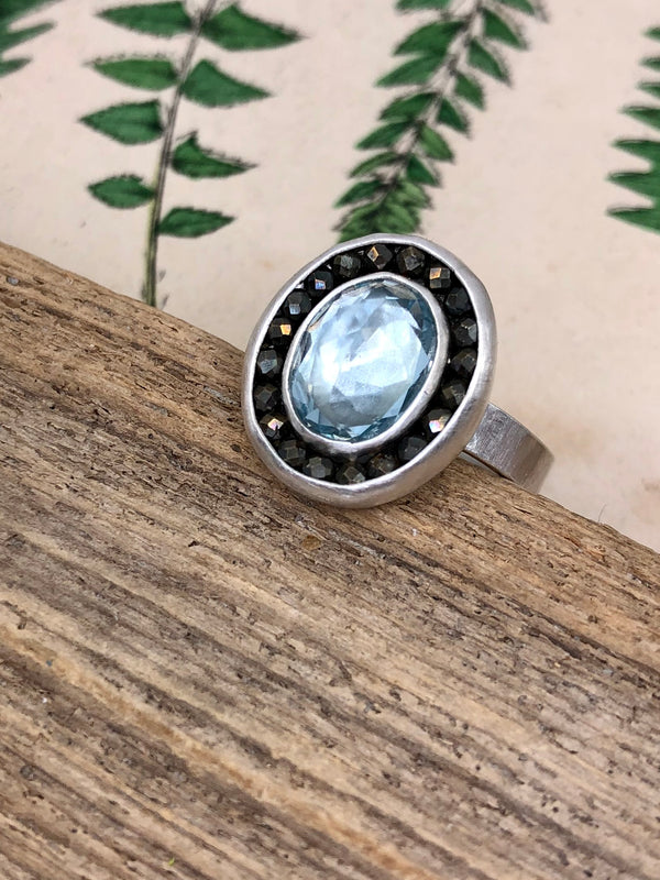 A gem quality aquamarine oval is surrounded by a halo of microfaceted pyrite gems. Set in sterling and fine silver. Size 7  • 1 8x6mm oval aquamarine  • Micro-faceted pyrite gems  • Sterling and fine silver•  • Size 7