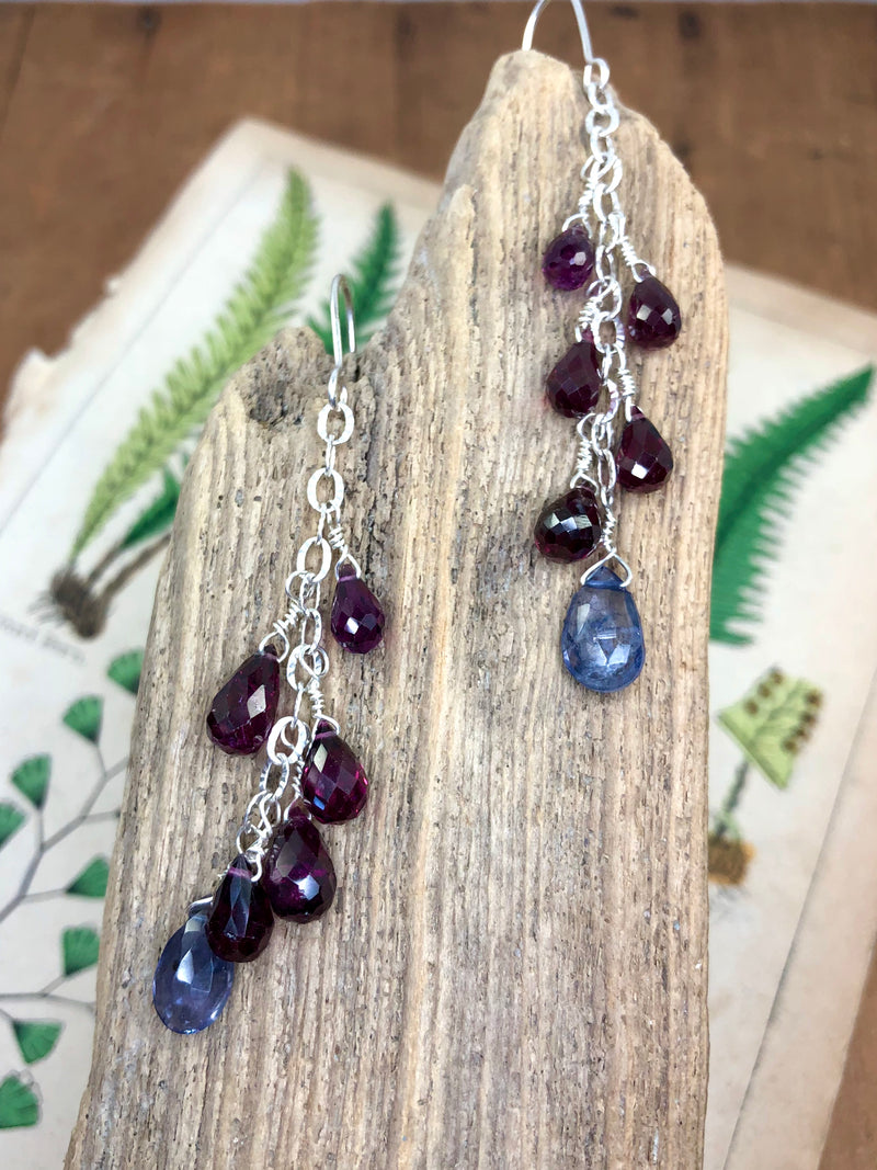 "Perfectly crimson rhodolite garnets are displayed on fancy silver chain with a beautiful iolite gem at their focal point. Approximately 2.5"" from the hook and finished on sterling French wires.  • 8 - rhodolite garnet briolettes  • 2 - iolite briolettes  • Fancy silver chain • Sterling French wires"