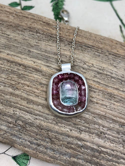 A rose cut bi-color tourmaline is surrounded by a halo of microfaceted ombré pink tourmalines and sterling and fine silver.  • Rose cut bi-color tourmaline  • Shades of pink tourmaline gems • Sterling and fine silver  • Tube bail