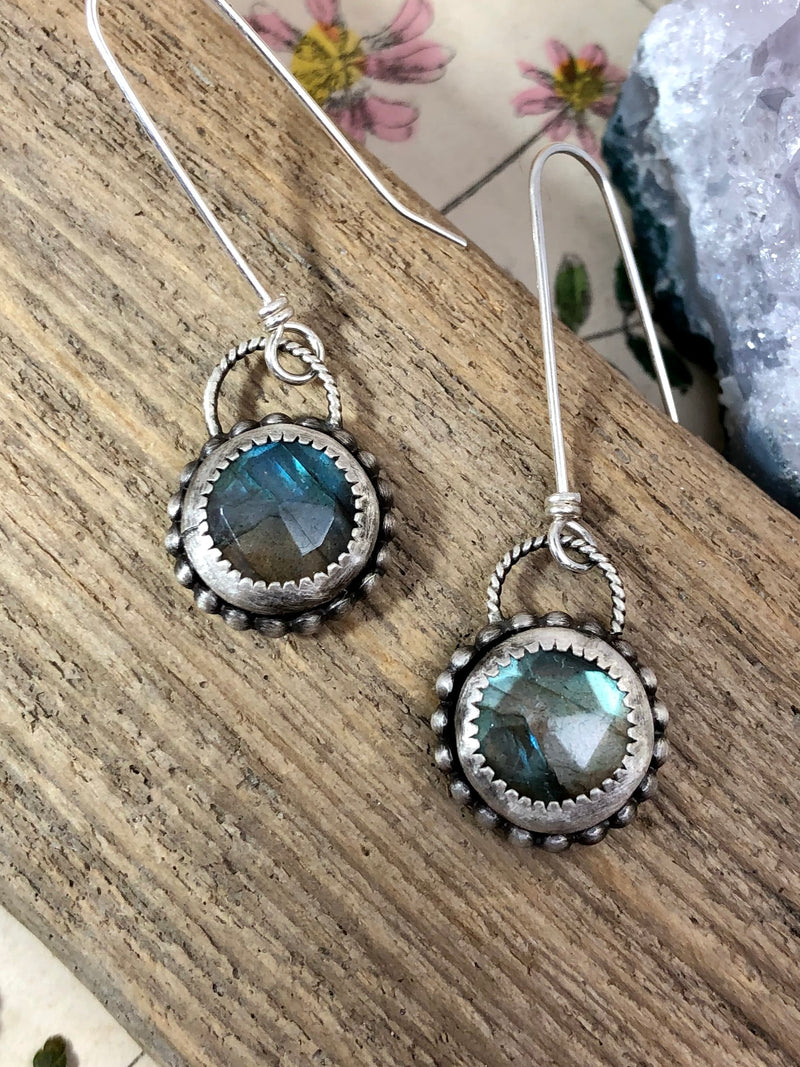 """Compassion is an action word with no boundaries"" - Prince  Revel in shimmery perfection of color and light. Green-blue faceted Labradorite gems set in hand-fabricated silver. The settings feature a serrated bezel thats gives way to a playful silver beaded halo, topped with twisted sterling wire and extra-long French wires. Prepare to dazzle!  Product Details:  • Extra-long sterling silver ear wires • Two round faceted Labradorite Gems • Sterling and fine silver • Just over 1/2"" long a"