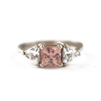 Pink princess cut engagement ring with triangle cut white sapphire side stones