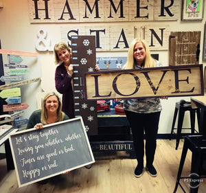 3 women hold signs made at Hammer & Stain North Aurora