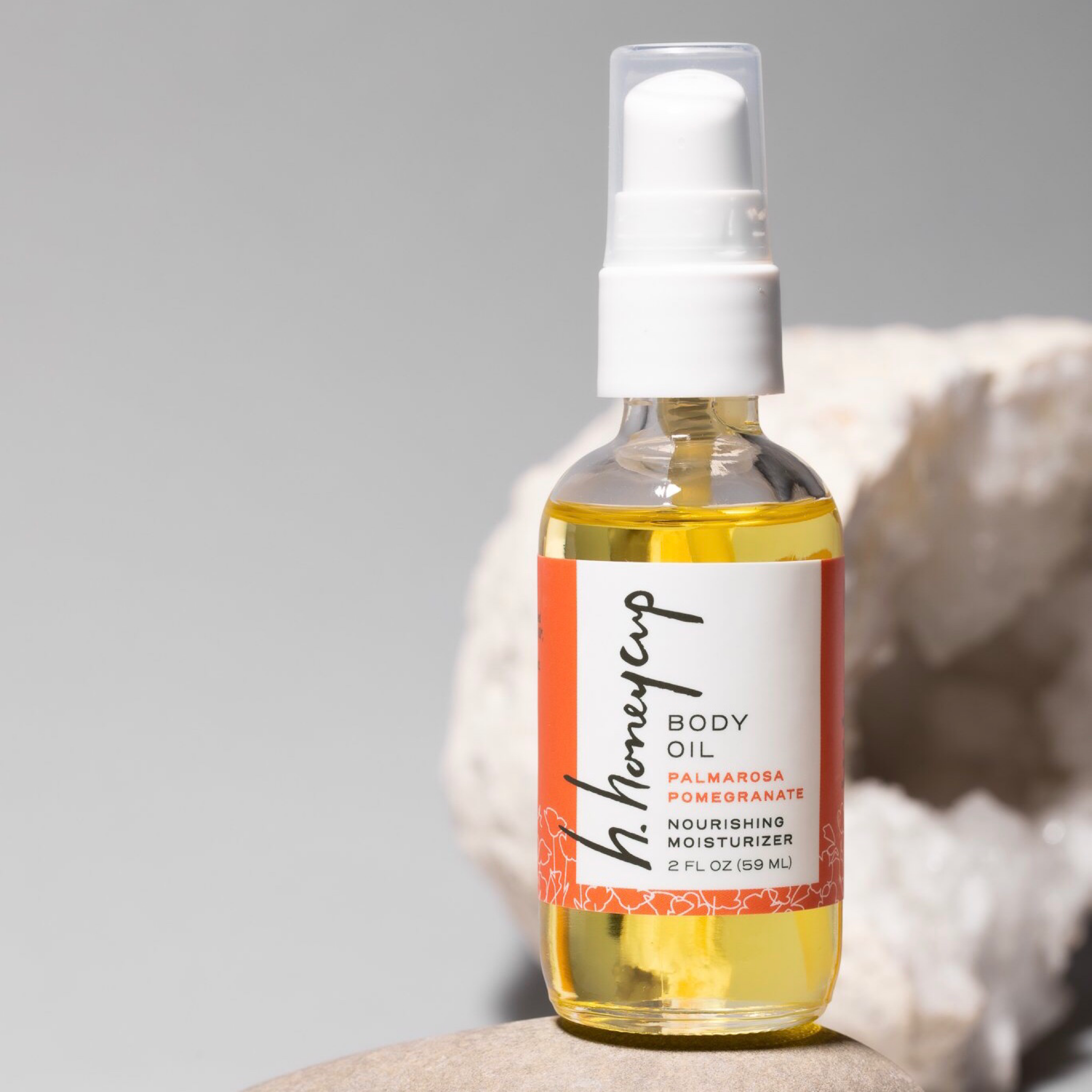 Natural body oil with palmarosa and lavender essential oils in 2 oz recyclable clear glass bottle with white spray top