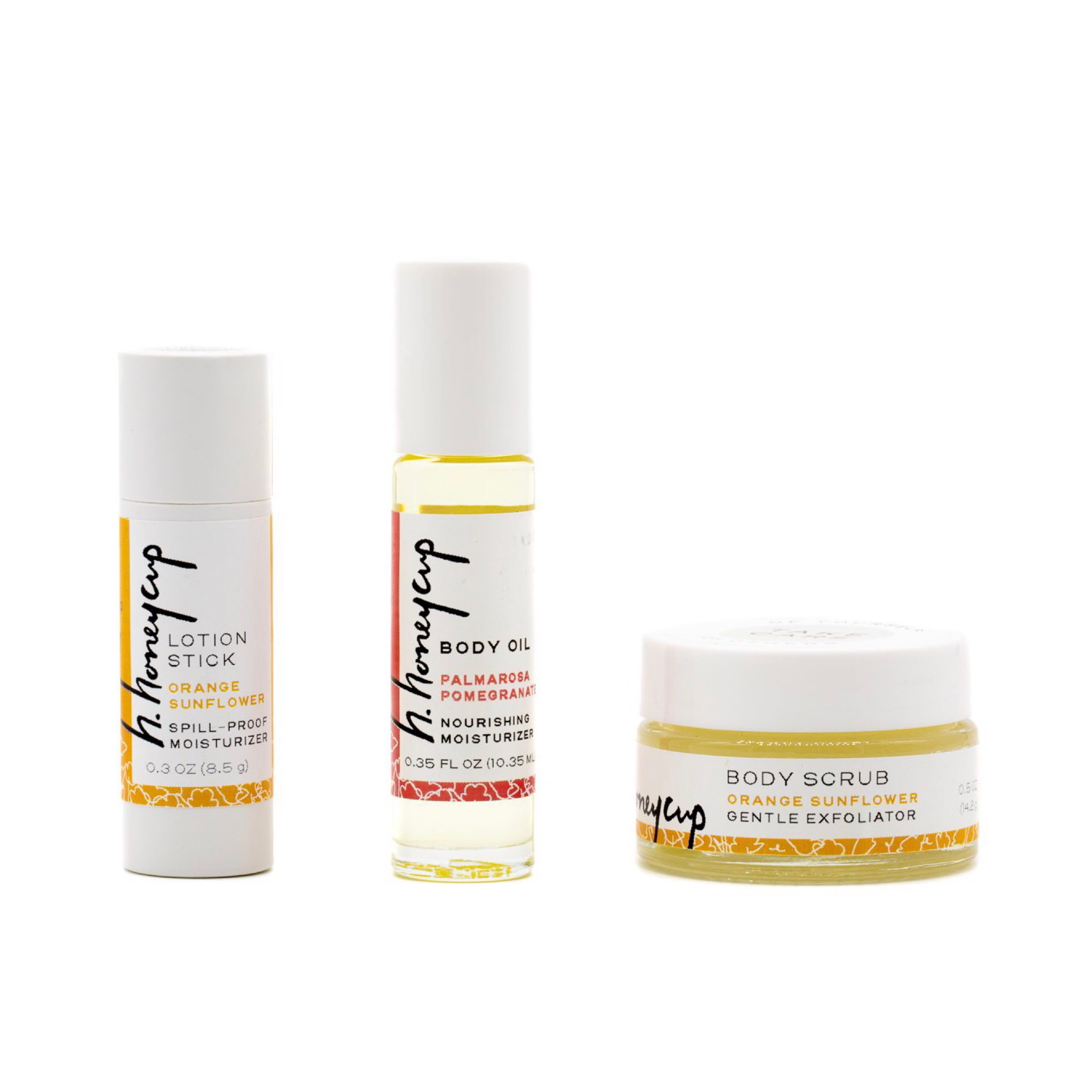 Floating product image of three skincare sample sizes of orange body scrub, lavender body oil and orange lotion stick