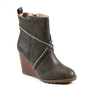 A faux stacked wedge heel enhances the character of this stylish vegan leather bootie. Stay stylish no matter the season in a rich olive green vegan leather upper that features a stitched cross strap that covers the vamp. AR TIST by Diba London seals the