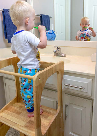 Child standing on a learning toddler tower brushing teeth in the bathroom