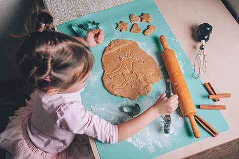 Kid cutting cookie dough shapes