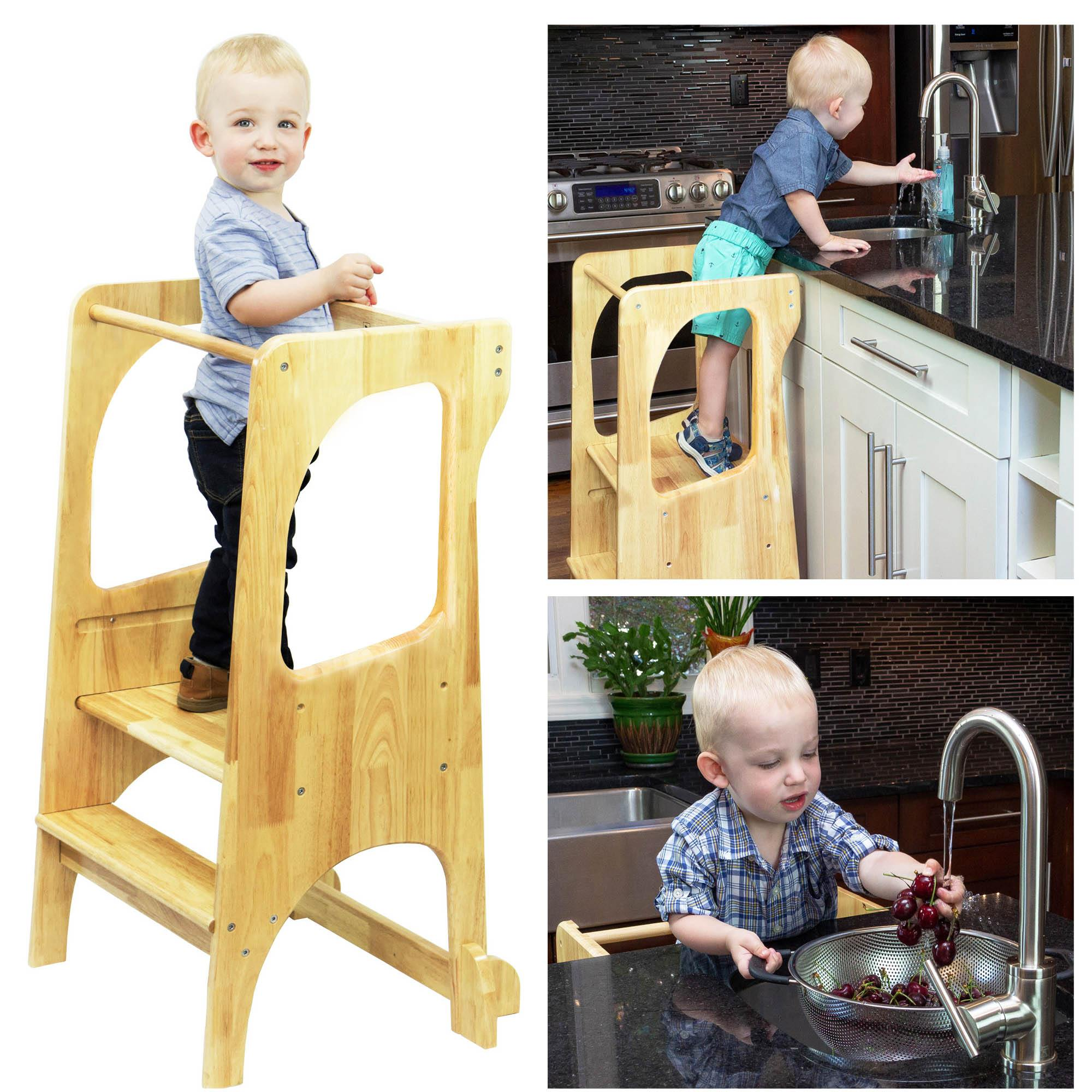 Kid standing on learning toddler tower in kitchen cooking