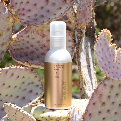 Purifying Botanical Wash 120ml photographed on a Prickly Pear Cactus. Product is by Mikel Kristi Skincare, based in the Arizona desert. This product is Step 1: Cleanse, and comes in a 120ml aluminum pump bottle with metallic gold colored label.