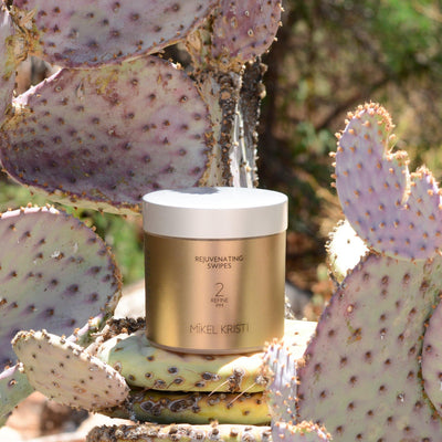 Rejuvenating Swipes 50 count. Photographed on a Prickly Pear Cactus. Product is by Mikel Kristi Skincare, based in the Arizona desert. This product is Step 2: Refine, and comes in a air sealed jar with screw on lid with metallic gold colored label.