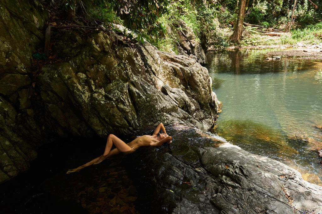 KaneSkennar-Woman lying on waterfall in nature