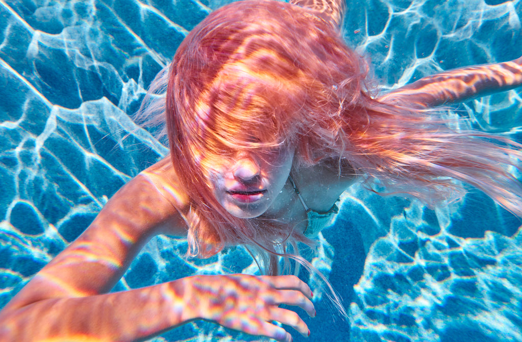KaneSkennar-Girl underwater with pink hair swimming to camera