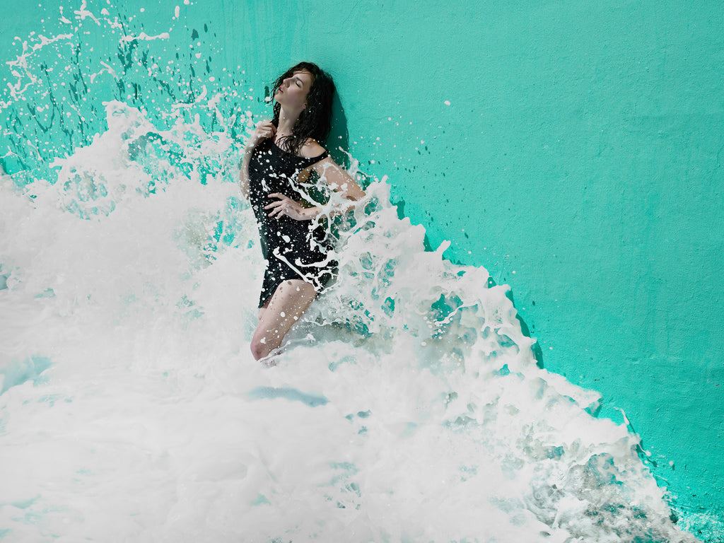 KaneSkennarphotographer-Wave splashing against wall with woman standing against it