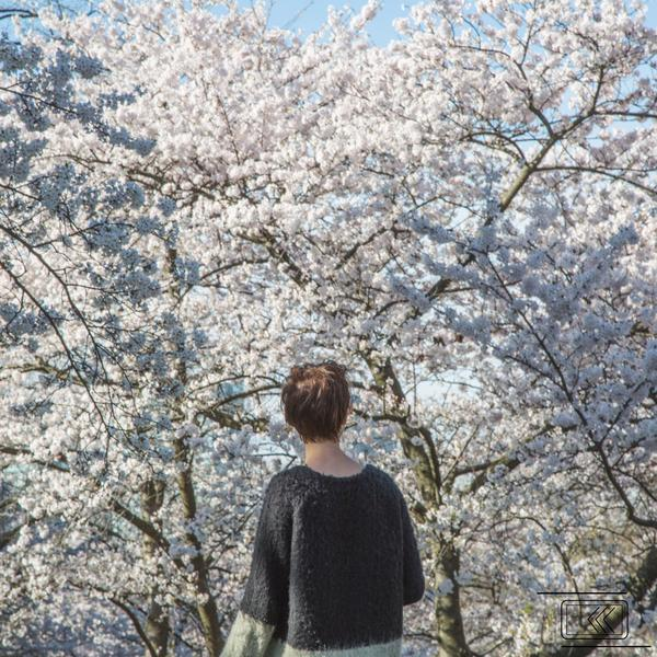 Woman standing outside during spring looking at trees
