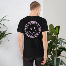 Load image into Gallery viewer, man wearing a black round neck t shirt and pink design of a melted smiley face