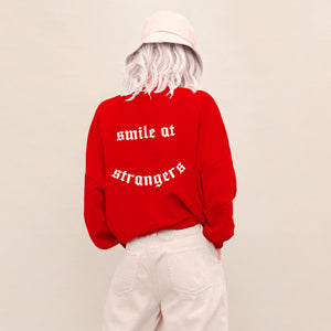 girl wearing a red crew neck long-sleeve sweatshirt and white printed design at the chest