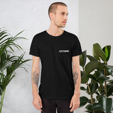 Load image into Gallery viewer, man wearing a black round neck t shirt