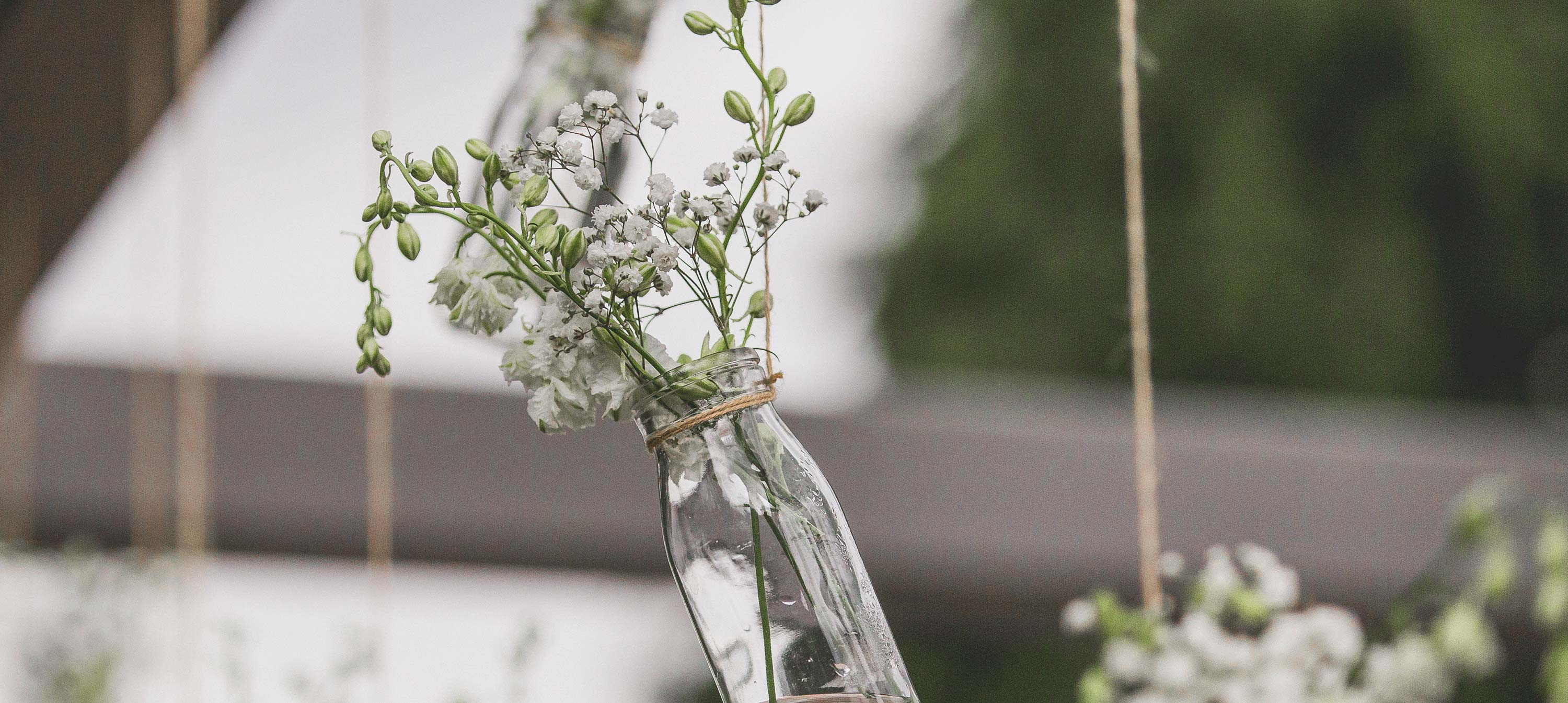 Flowers hanging in clear glass milk bottles wedding decorations