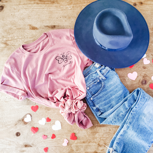 mauve tee shirt with bee design and blue hat and jeans on table