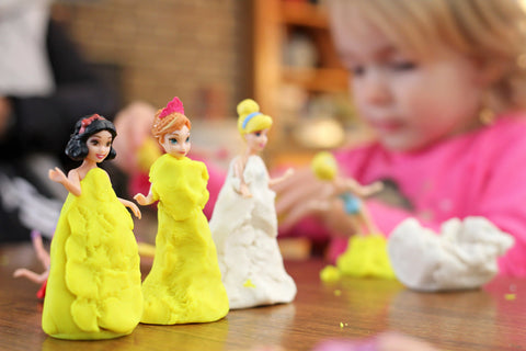 princess characters dressed up in yellow play dough dresses with child blurred in background made with 100% non toxic play dough in canada dough parlour