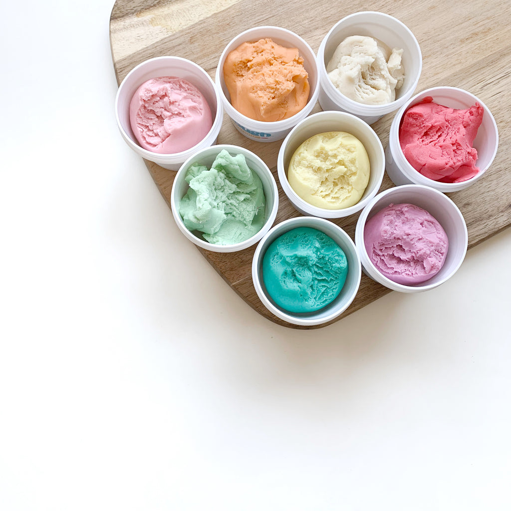 8 tubs of multicoloured dough in tubs sitting on wooden cutting board on a white table