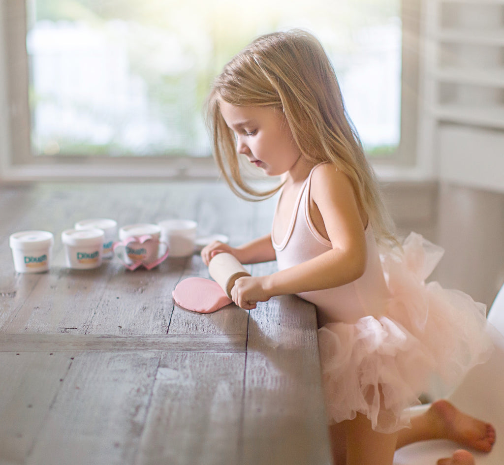 little girl dressed in pink rolling pink dough on a table with a rolling pin, tubs of dough and pink heart cutters are in the background