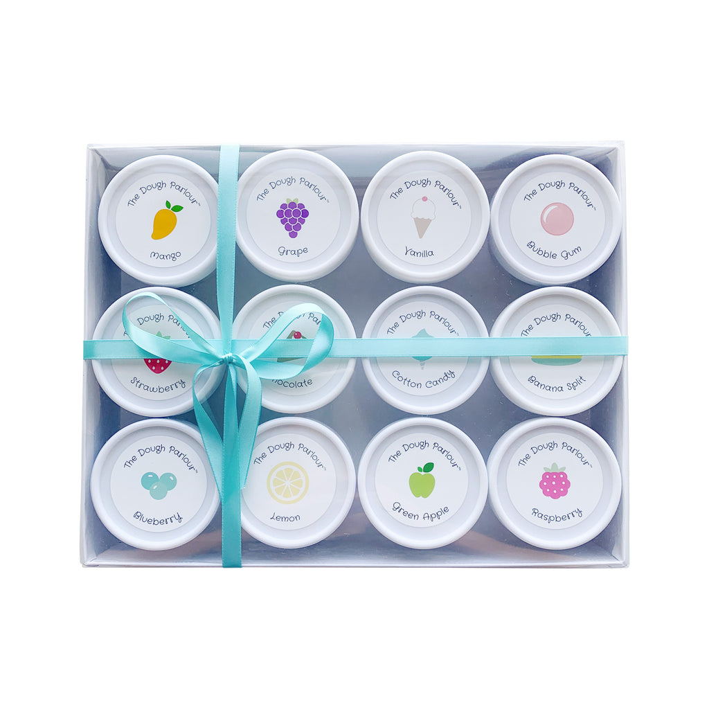 The Dough Parlour Collector's Gift box holds 12 tubs of scented dough in a white box with a clear lid and teal ribbon shown on white background