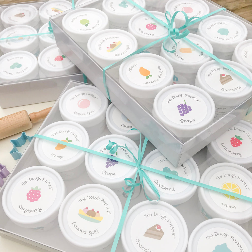 packages and cases tied in turquoise ribbon of white play dough containers that are 100% non-toxic play dough