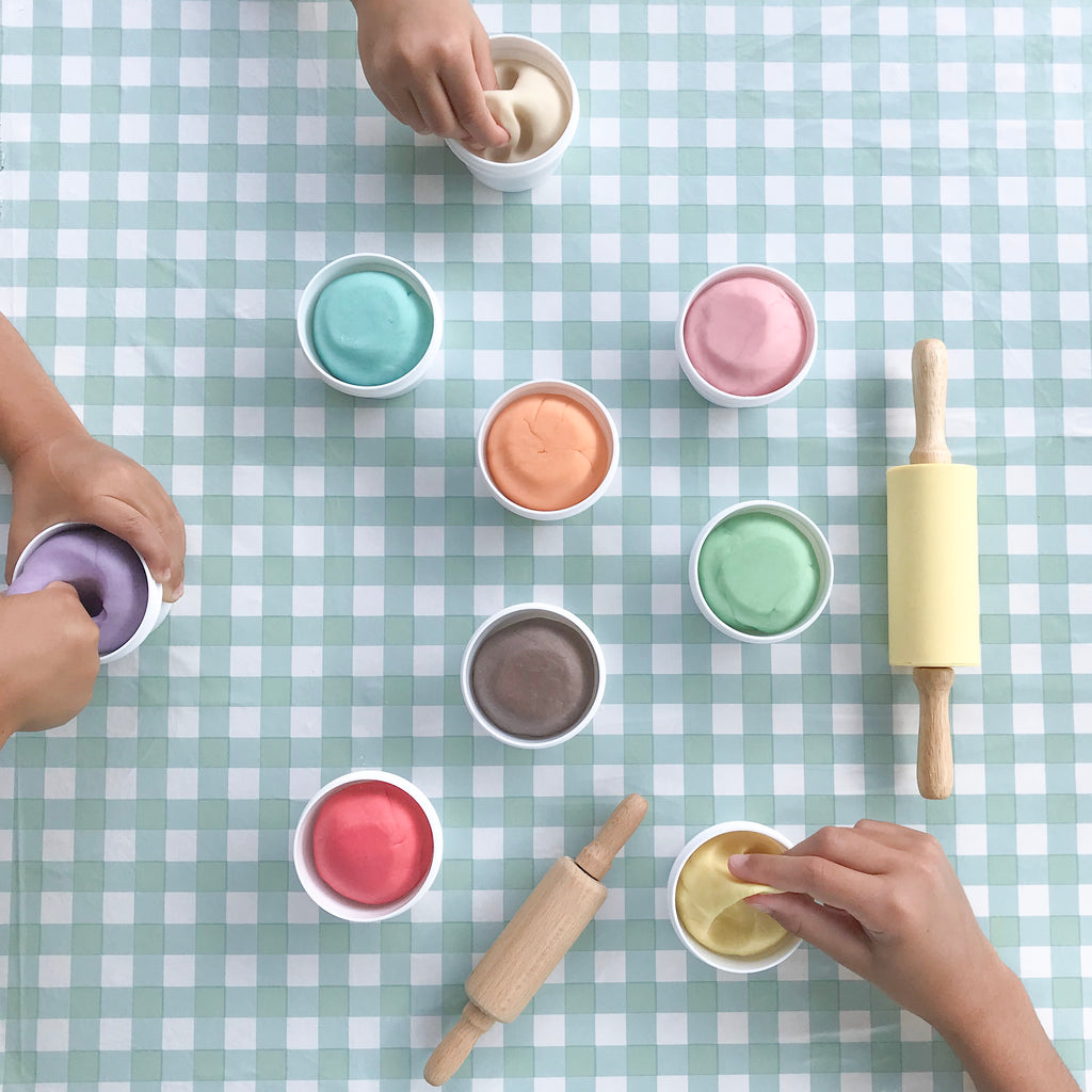 checkerboard table with rolling pins and multiple pots of colourful dough, children's hands squishing the dough in the pots