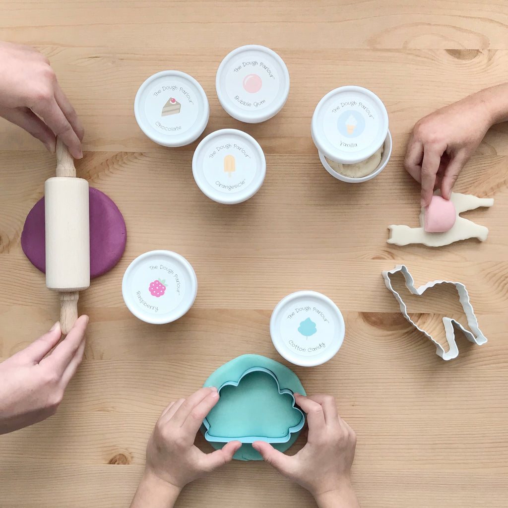 three sets of little hands playing with a rolling pin and cutters, multiple tubs of dough sitting on the table