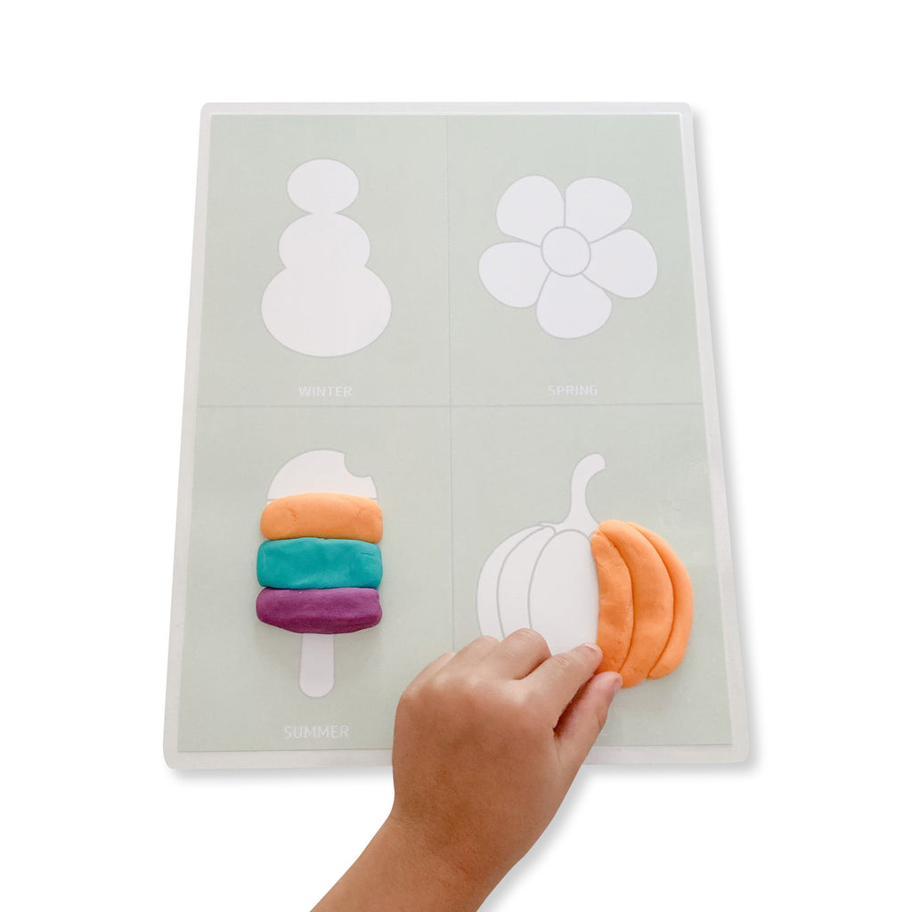 Child playing with the Four Seasons mat with dough