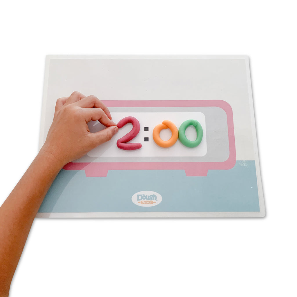 Child playing with the Telling Time mat with dough