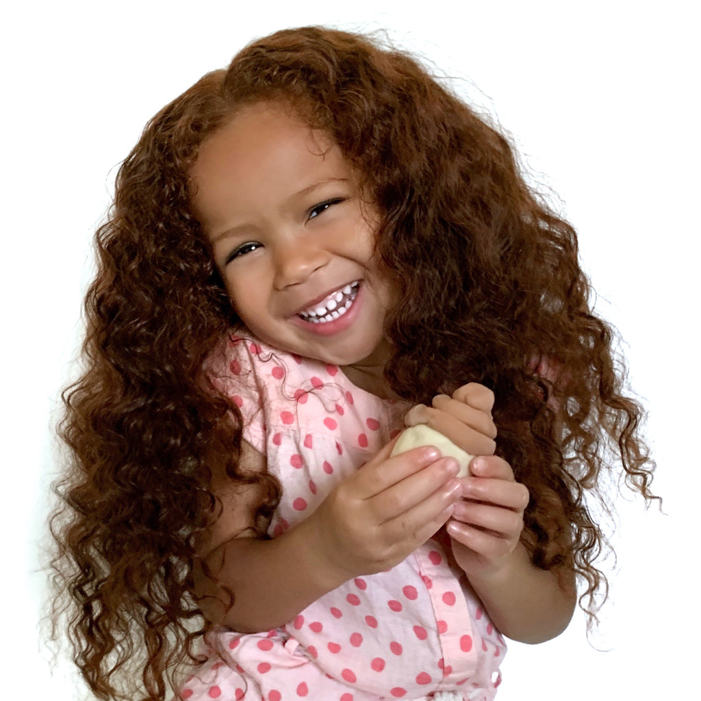 little girl smiling for the camera and holding a dough sculpture of a cupcake