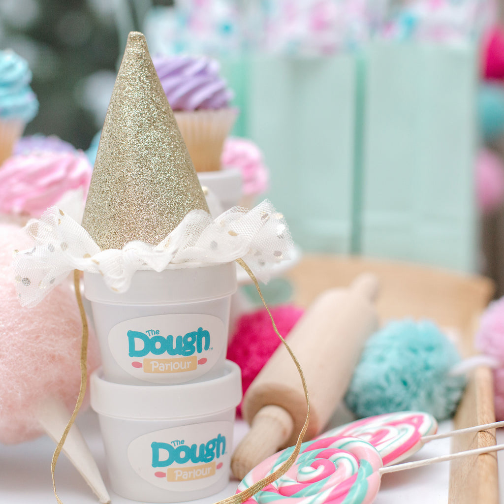 Two tubs of dough stacked with a glitter party hat on top, background shows candy and party decorations