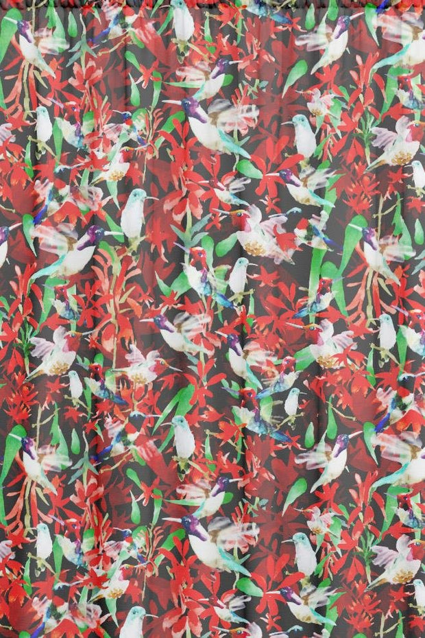 Red animal patterned fabric featuring hummingbirds in flight in front of red floral background.