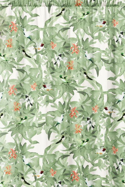 Green animal patterned fabric featuring hummingbirds in flight against a background of green foliage with red flowers.