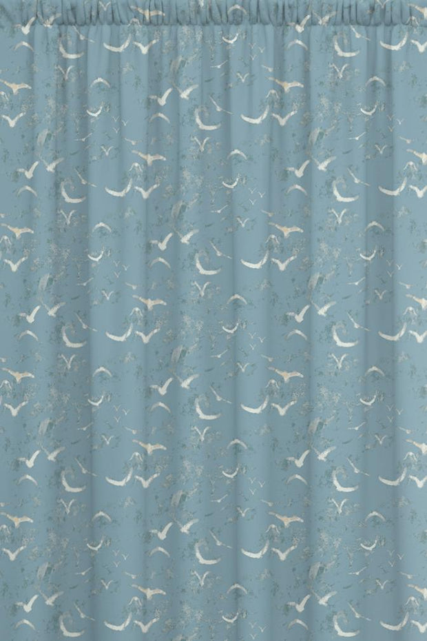 Dusky blue animal pattern fabric featuring birds in flight.