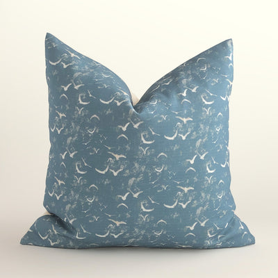 Decorative dusky blue throw pillow featuring an abstract pattern design of birds in flight.
