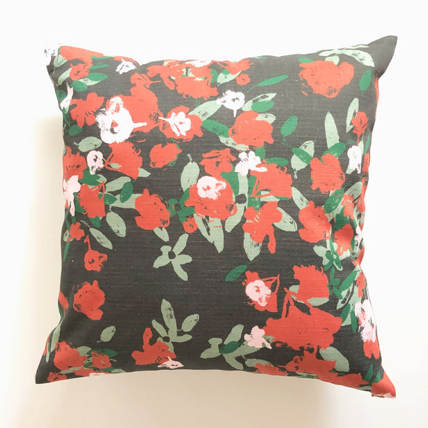 Decorative red and black throw pillow featuring a floral pattern design.  Edit alt text