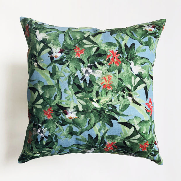 Decorative green throw pillow featuring an animal pattern design of hummingbirds in flight.