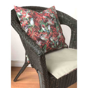 Decorative red and green throw pillow featuring an animal pattern design of hummingbirds, placed on chair.