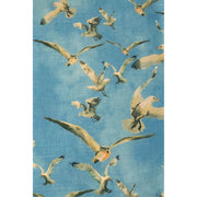 Detail of decorative blue throw pillow featuring an animal pattern of seagulls in flight.