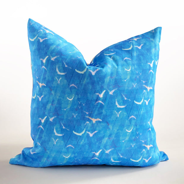 Decorative blue throw pillow featuring an abstract pattern design of birds in flight.  Edit alt text