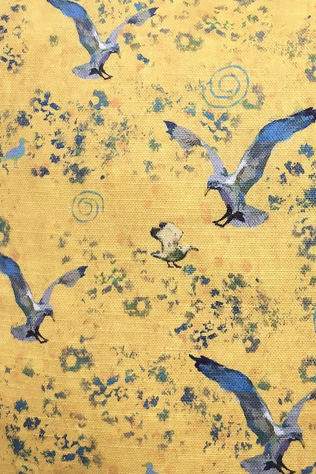 Detail of decorative yellow throw pillow featuring an animal pattern design of birds in flight.